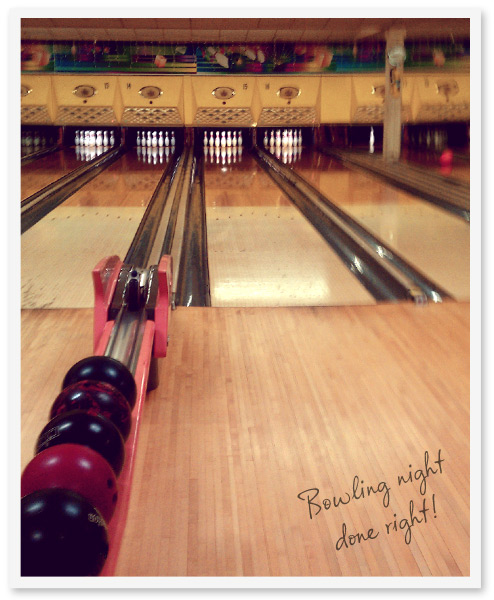 photo of a bowling alley lane with bowling balls lined up in the rack.