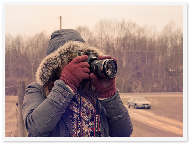photo of a person in a parka holding a camera and taking a photo