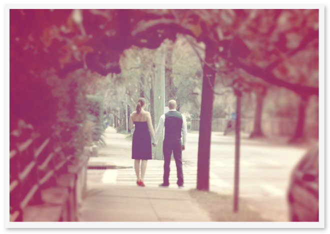 Soft focus photo of two people walking along a path and holding hands