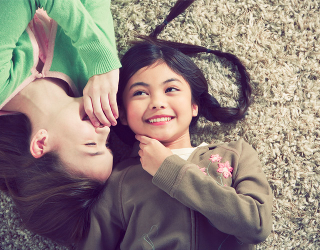 photo of two kids lying on the carpet while smiling and laughing together