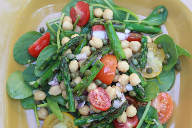 A bowl of salad made with asparagus, cherry tomatoes, chickpeas, and spinach greens