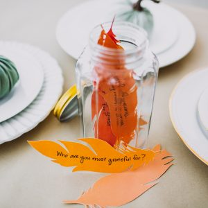 feathers in a jar stating what you're thankful for