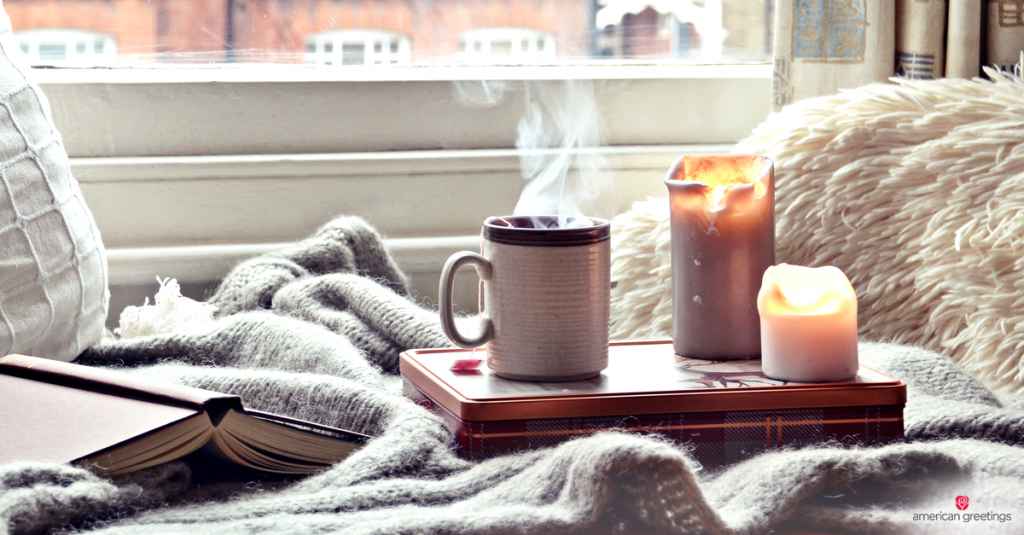 A cozy Hygge place shown with soft blankets, warm coffee, the glow of candlelight and a good book.