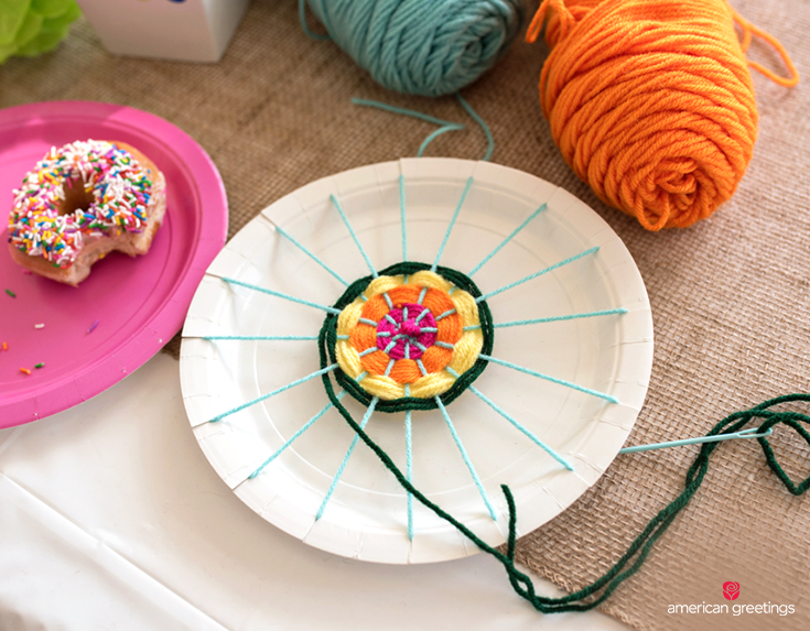 A DIY craft made with yarn and a paper plate with hygge design elements.